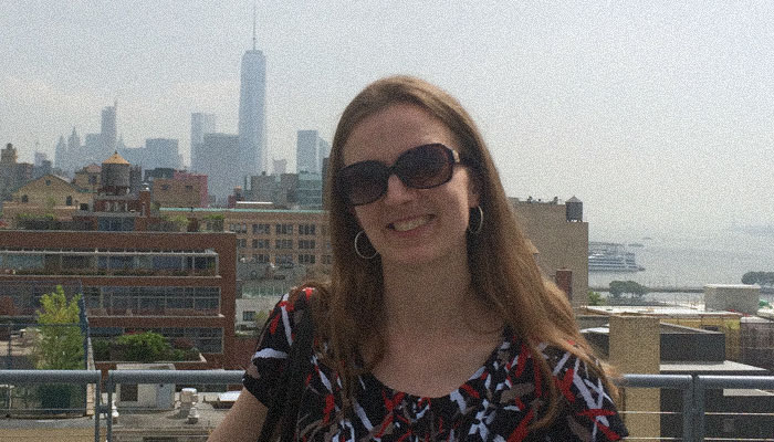 Sveta standing on a rooftop with downtown Manhattan in background