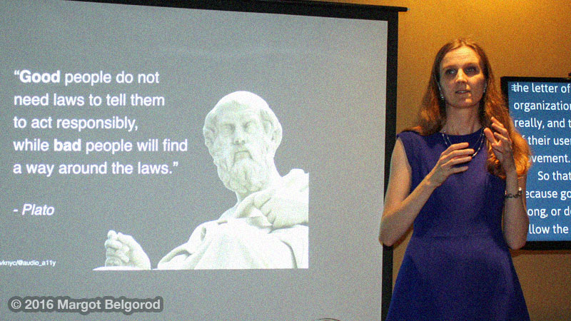 Svetlana in a blue dress standing between a screen with live captions and a screen with a slide showing Plato's quote.