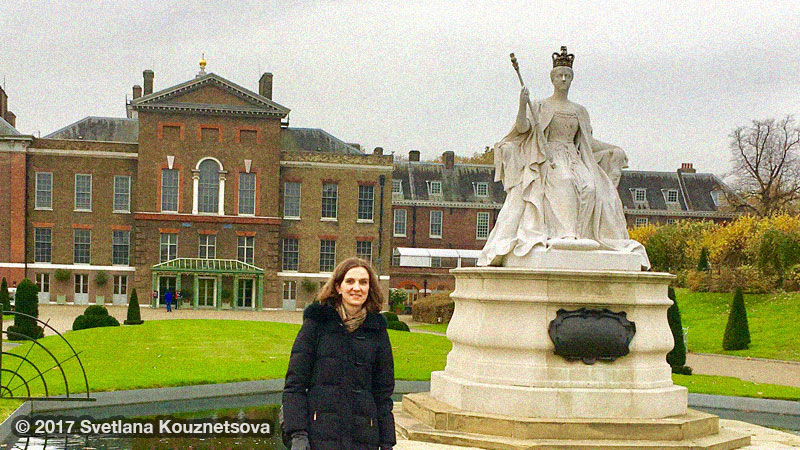Svetlana standing in Kensington Gardens in front of Victoria statue and Kensington Palace.