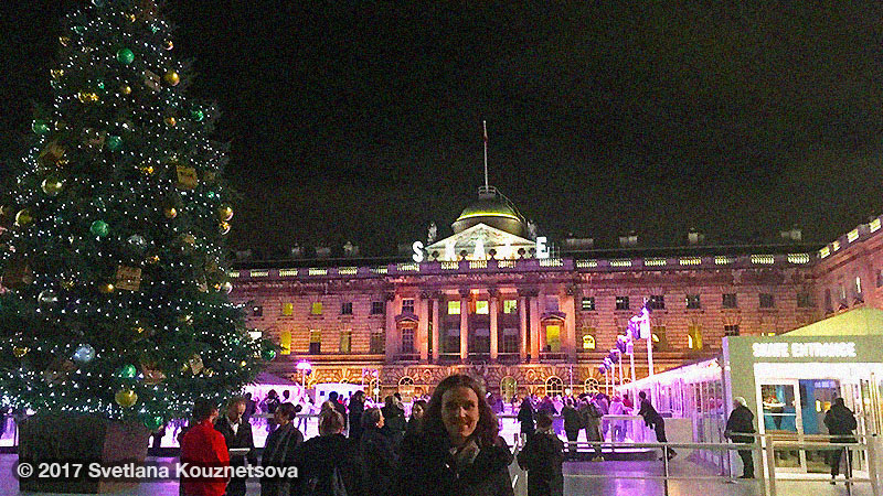 Svetlana standing in front of a Christmas tree and a skating rink at Somerset House in London